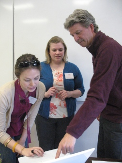 Teacher Leaders Andria Chase and Sarah Williams take a closer look at workshop info with Leadership team member Jeff Beaudry